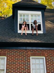 2 friends sitting on top of a window