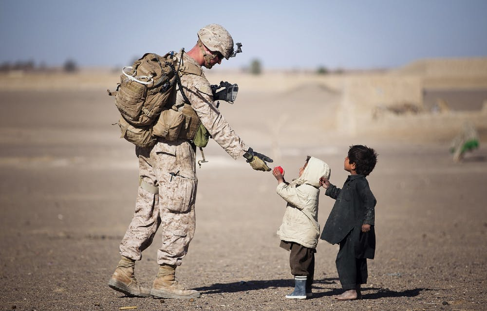 Unicef military is talking to children in the desert.